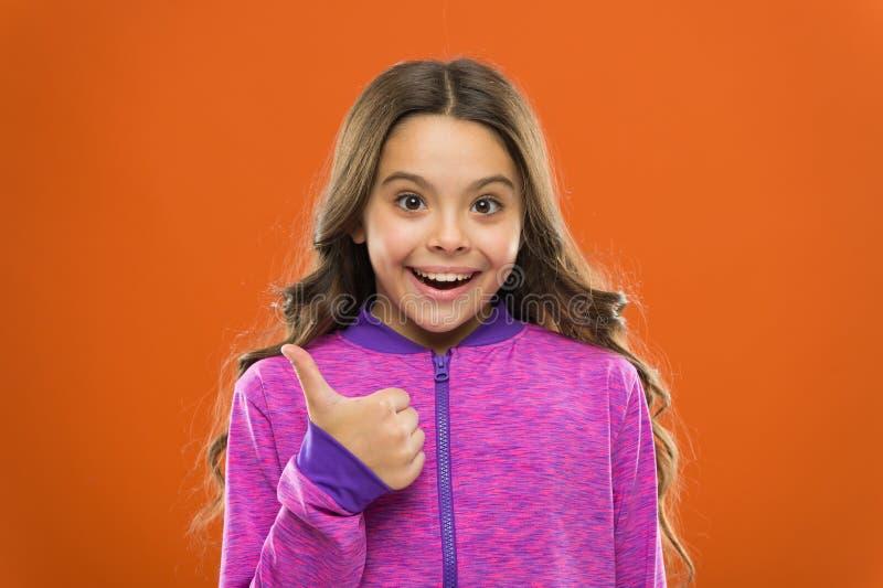 Το χαριτωμένο παιδί κοριτσιών παρουσιάζει αντίχειρες επάνω στη χειρονομία Τα δώρα τα teens σας θα αγαπήσουν συνολικά Τα παιδιά συ στοκ φωτογραφία