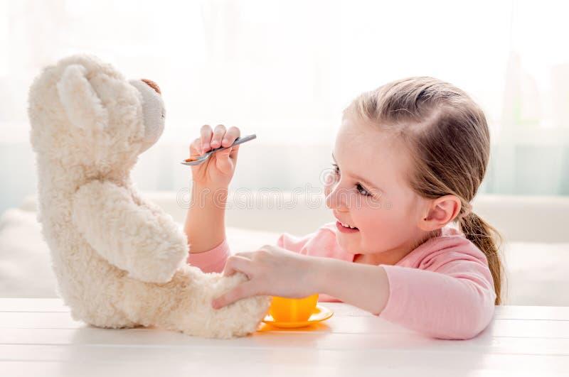 Το χαριτωμένο παιχνίδι σίτισης μικρών κοριτσιών teddy αντέχει στοκ εικόνες με δικαίωμα ελεύθερης χρήσης
