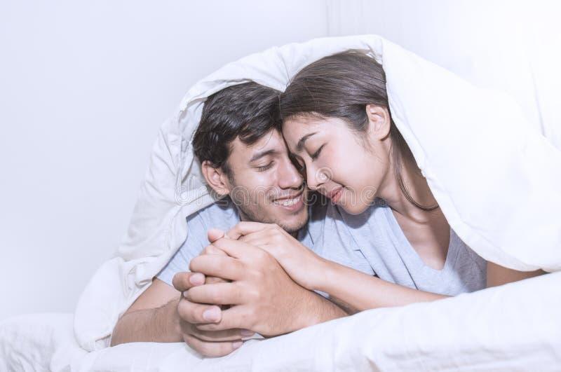 Το χαριτωμένο ρομαντικό ζεύγος κάτω από ένα κρεβάτι καλύπτει στοκ φωτογραφία με δικαίωμα ελεύθερης χρήσης