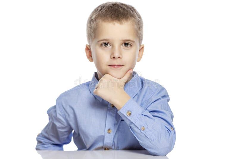 Το χαριτωμένο σοβαρό αγόρι της ηλικίας κάθεται στον πίνακα E στοκ εικόνες