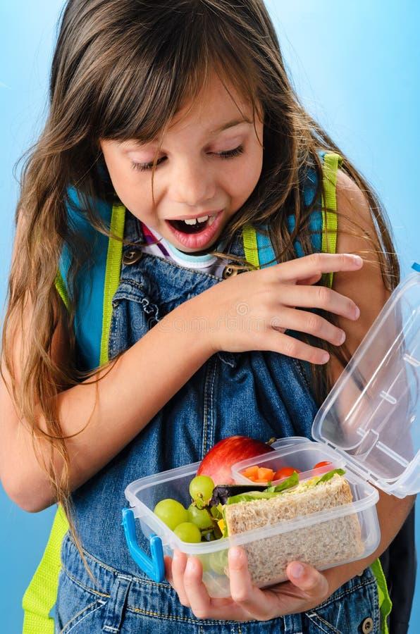 Το χαριτωμένο σχολικό κορίτσι είναι έκπληκτο να δει τι είναι μέσα στο υγιές λ της στοκ εικόνες με δικαίωμα ελεύθερης χρήσης