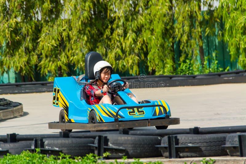 Το χαριτωμένο ταϊλανδικό κορίτσι οδηγεί πηγαίνει -πηγαίνω-kart στοκ εικόνες