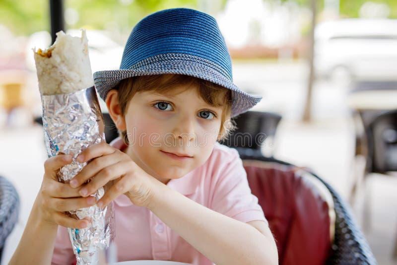 Το χαριτωμένο υγιές προσχολικό αγόρι παιδιών τρώει την τουρκική συνεδρίαση kebab στον καφέ υπαίθρια στοκ φωτογραφίες με δικαίωμα ελεύθερης χρήσης