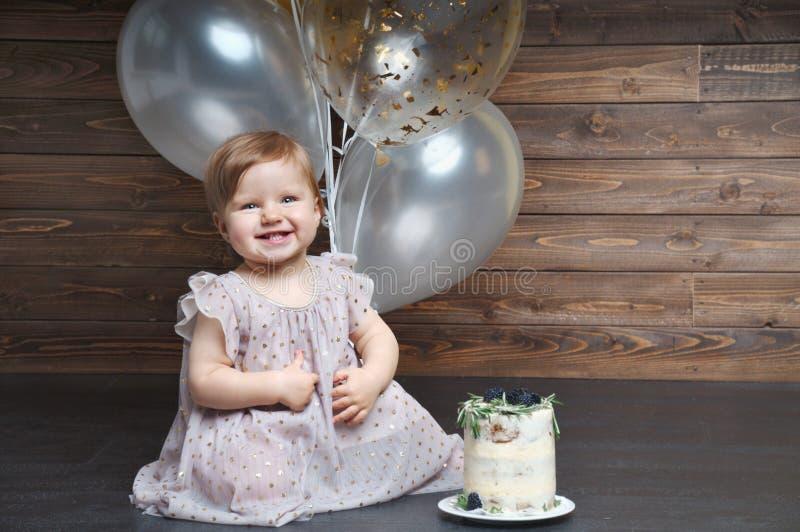 Το χαριτωμένο χαμογελώντας μικρό κορίτσι γιορτάζει την πρώτη γιορτή γενεθλίων της με τα μπαλόνια και το κέικ στοκ φωτογραφία