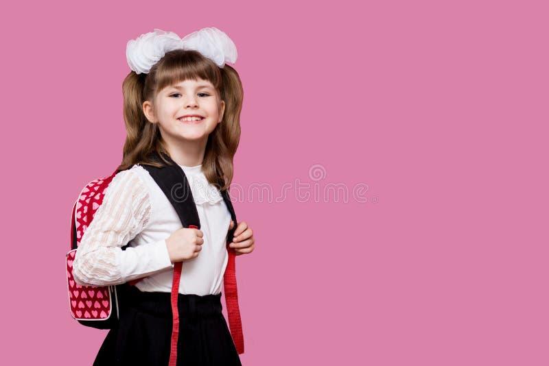 Το χαριτωμένο χαμογελώντας μικρό κορίτσι στη σχολική στολή και το λευκό υποκύπτει με το σακίδιο πλάτης στο ρόδινο υπόβαθρο πίσω σ στοκ εικόνα