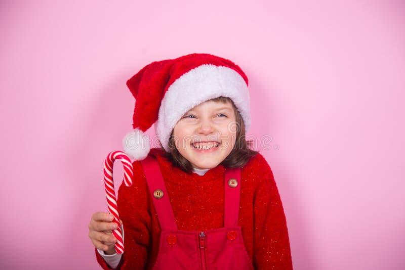 Το χαριτωμένο χαμογελώντας μικρό κορίτσι στο καπέλο Santa και την καραμέλα εκμετάλλευσης κοστουμιών Χριστουγέννων μπορεί στο στού στοκ εικόνες