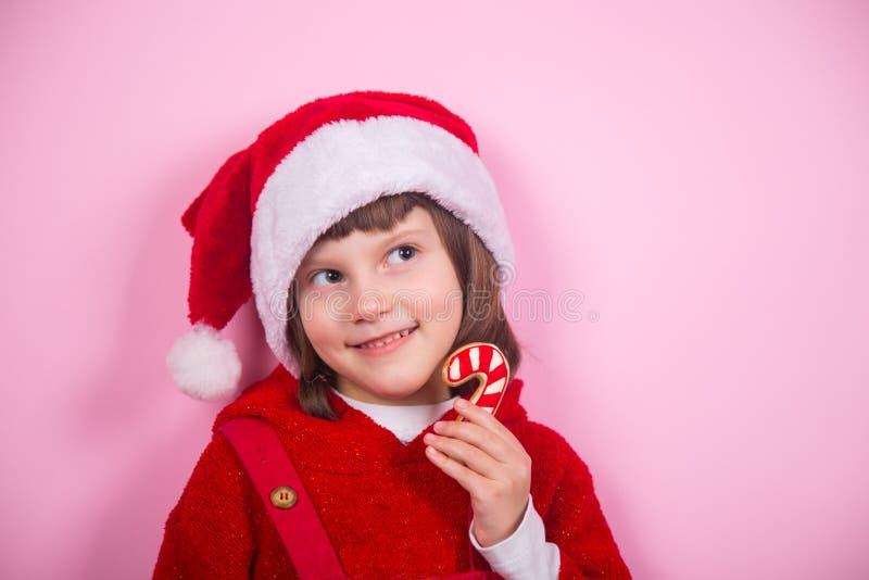 Το χαριτωμένο χαμογελώντας μικρό κορίτσι στο καπέλο Santa και την καραμέλα εκμετάλλευσης κοστουμιών Χριστουγέννων μπορεί στο στού στοκ εικόνες με δικαίωμα ελεύθερης χρήσης