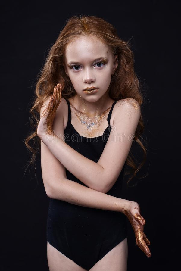 Το χαριτωμένο redhead εφηβικό πρότυπο με το φωτεινό makeup και ζωηρόχρωμος ακτινοβολεί και σπινθηρίσματα στο πρόσωπο και το σώμα  στοκ φωτογραφίες με δικαίωμα ελεύθερης χρήσης