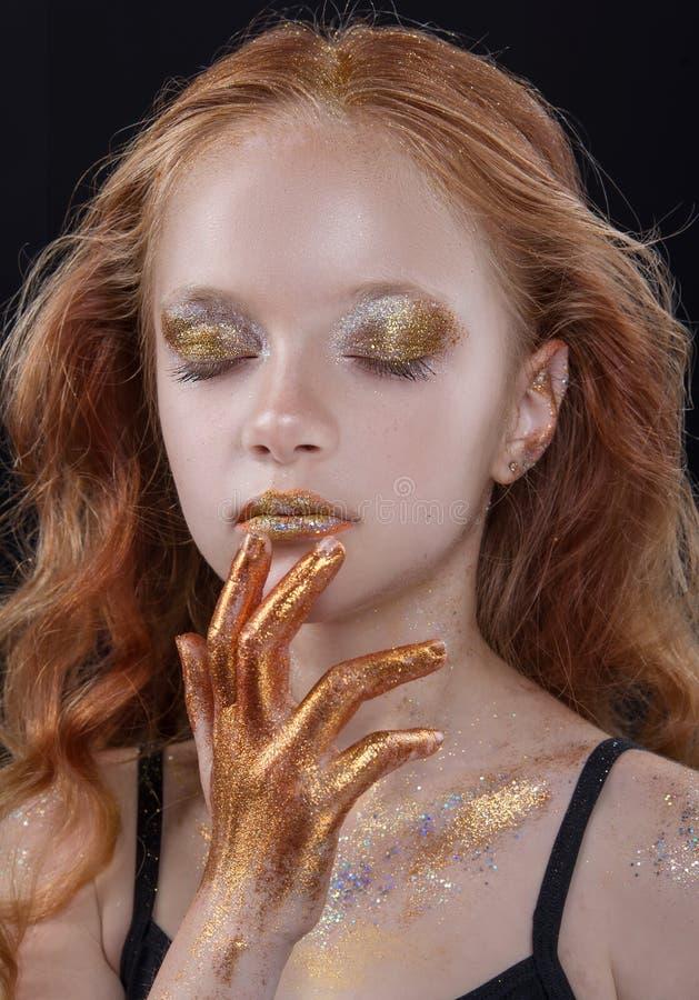 Το χαριτωμένο redhead εφηβικό πρότυπο με το φωτεινό makeup και ζωηρόχρωμος ακτινοβολεί και σπινθηρίσματα στο πρόσωπο και το σώμα  στοκ φωτογραφία με δικαίωμα ελεύθερης χρήσης