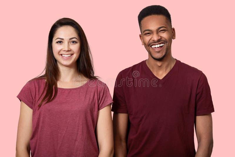 Το χαρούμενο θετικό χαμόγελο ανδρών και γυναικών αφροαμερικάνων ευρέως στη κάμερα, ντύνει τη διασκέδαση μαζί, στα περιστασιακά εν στοκ εικόνα