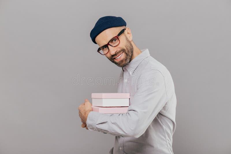 Το χαρούμενο χαμογελώντας γενειοφόρο άτομο με την ευτυχή έκφραση, σκοτεινή σκληρή τρίχα, φορά το άσπρο πουκάμισο και τα θεάματα,  στοκ εικόνες με δικαίωμα ελεύθερης χρήσης