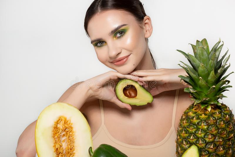 Το χαρούμενο όμορφο κορίτσι με τη φωτεινή εκμετάλλευση τέχνης makeup τεμάχισε το φρέσκο αβοκάντο υπό εξέταση κοντά στο πρόσωπο, φ στοκ φωτογραφίες