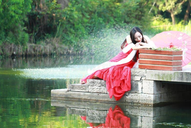 Το χαλαρωμένο ασιατικό κινεζικό κορίτσι απολαμβάνει το ελεύθερο χρόνο στοκ εικόνες