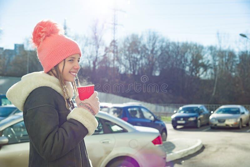 Το χειμερινό ηλιόλουστο υπαίθριο πορτρέτο του έφηβη που φορά ένα παλτό και πλέκει το καπέλο με το φλυτζάνι του ζεστού ποτού στοκ φωτογραφίες με δικαίωμα ελεύθερης χρήσης