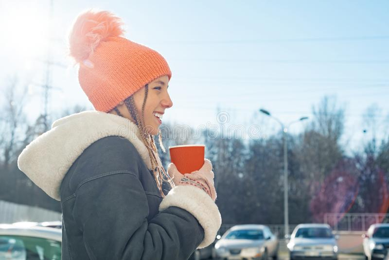 Το χειμερινό ηλιόλουστο υπαίθριο πορτρέτο του έφηβη που φορά ένα παλτό και πλέκει το καπέλο με το φλυτζάνι του ζεστού ποτού, διάσ στοκ φωτογραφίες