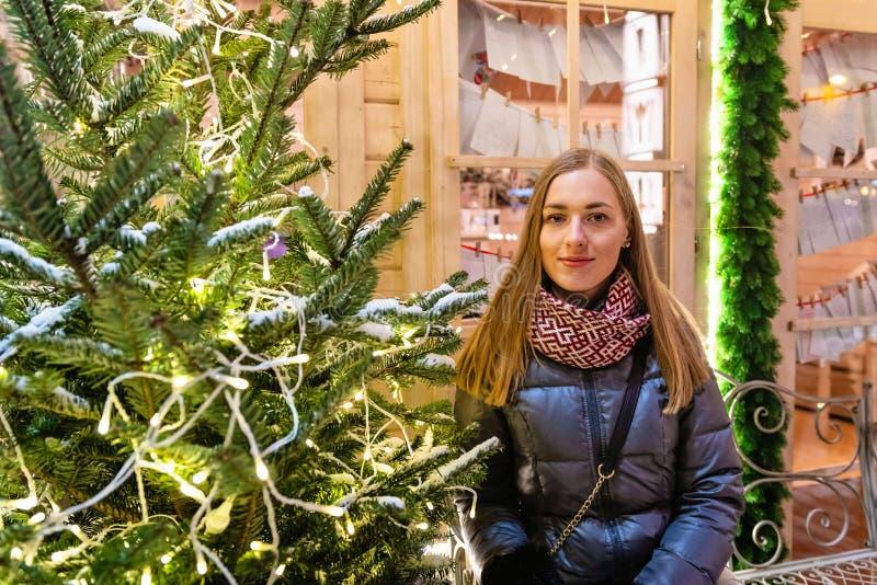 Το χειμερινό πορτρέτο του ευτυχούς νέου περπατήματος γυναικών στη χιονώδη πόλη διακόσμησε για τα Χριστούγεννα και τις νέες διακοπ στοκ φωτογραφίες