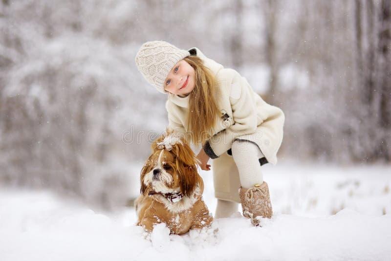 Το χειμώνα, το χιόνι εμπίπτει στο χιονώδες δάσος, παιχνίδι μικρών κοριτσιών με το σκυλί στοκ φωτογραφίες με δικαίωμα ελεύθερης χρήσης