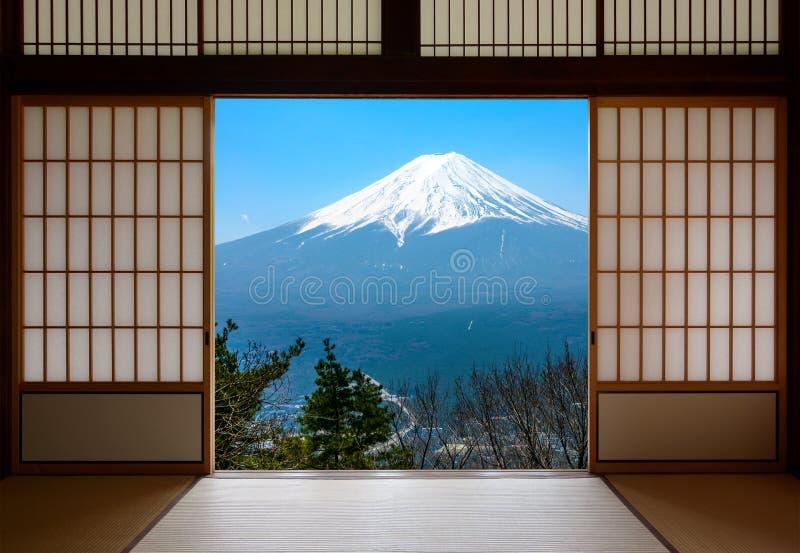 Το χιόνι που καλύπτεται τοποθετεί το Φούτζι στην Ιαπωνία που βλέπει μέσω των παραδοσιακών ιαπωνικών συρόμενων πορτών εγγράφου στοκ εικόνες με δικαίωμα ελεύθερης χρήσης