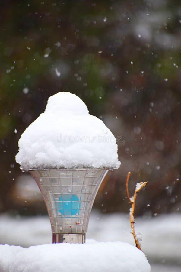 Το χιόνι στο λαμπτήρα οδών που μοιάζει με τον κώνο παγωτού με το άσπρο χιόνι ξεφλουδίζει στον αέρα - ενεργές χιονοπτώσεις κατά τη στοκ εικόνα