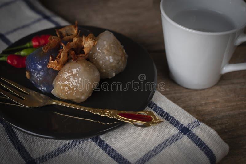 Το χοιρινό κρέας σάγου στο μαύρο πιάτο κύκλων με τηγανισμένο σκόρδου έχει την άσπρη πίσω πλευρά θέσεων φλυτζανιών και τη χρυσή θέ στοκ φωτογραφία