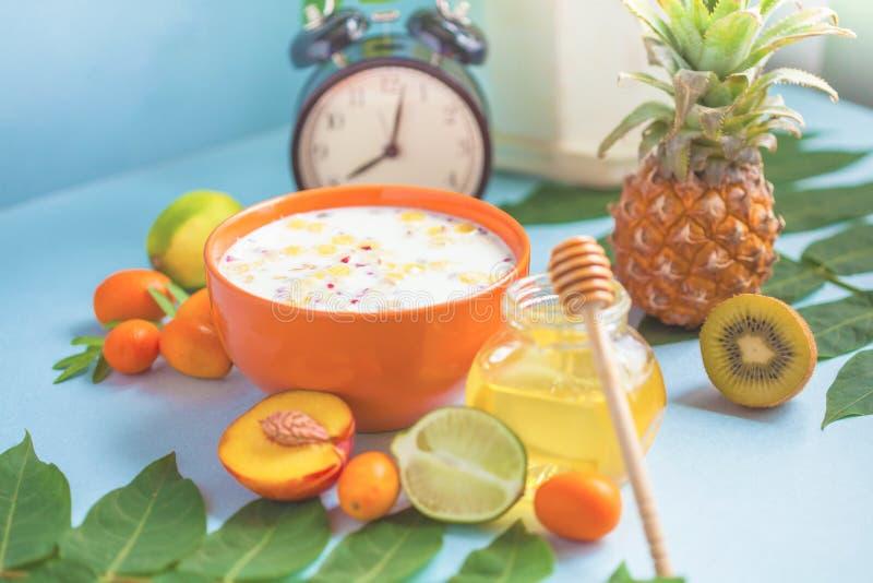 Το χρήσιμο πρόγευμα πρωινού, το muesli, το φλιτζάνι του καφέ μελιού ανανά ασβέστη ροδάκινων φρούτων και ένα ξυπνητήρι σε ένα μπλε στοκ φωτογραφία