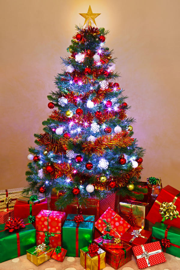 Το χριστουγεννιάτικο δέντρο και παρουσιάζει στο σπίτι στοκ φωτογραφία