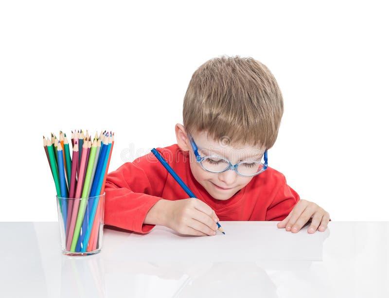 Το 5χρονο αγόρι στα μπλε σημεία κάθεται σε έναν άσπρο πίνακα και και σύρει τα μολύβια στοκ φωτογραφία με δικαίωμα ελεύθερης χρήσης