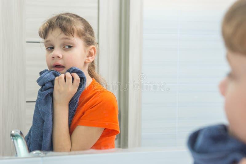 Το 7χρονο κορίτσι σκουπίζει το πρόσωπό της με την πετσέτα μετά από την πλύση στοκ φωτογραφίες