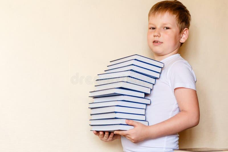 Το 8χρονο παιδί κρατά έναν σωρό των βιβλίων στοκ φωτογραφία