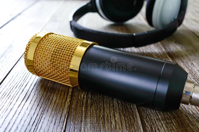 Το χρυσά μικρόφωνο και τα ακουστικά συμπυκνωτών βρίσκονται σε έναν ξύλινο πίνακα στοκ εικόνες