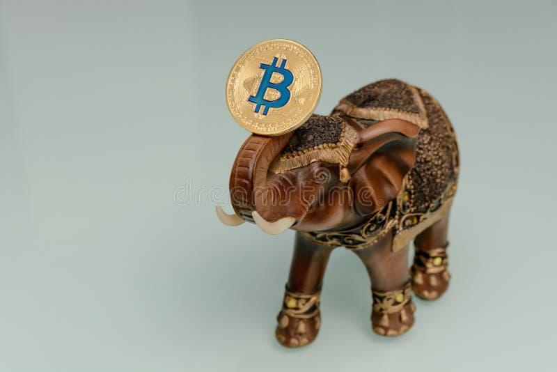 Το χρυσά bitcoin και το χέρι statuette του ελέφαντα στοκ εικόνα