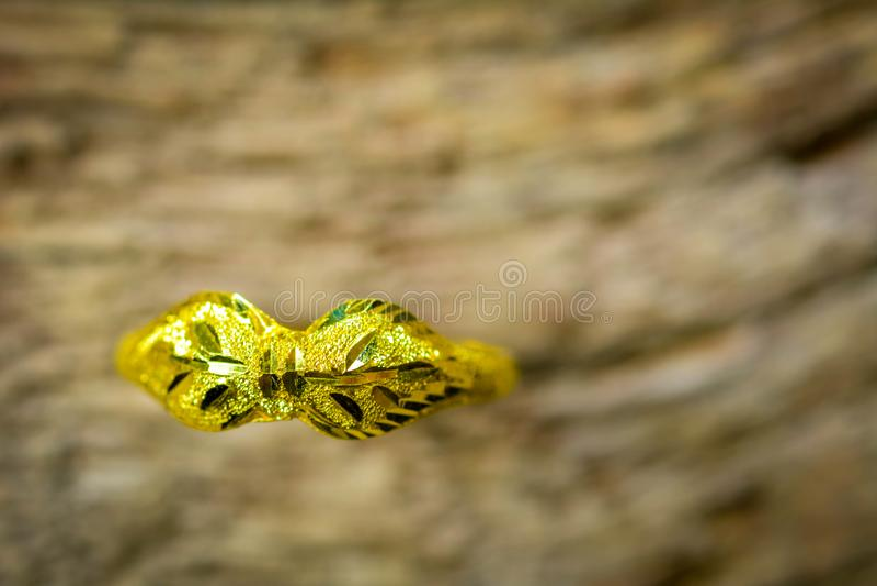 Το χρυσό δαχτυλίδι αρραβώνων εμπίπτει στο κρεβάτι και δεν μπορεί να βρεθεί και λάμποντας στο ξύλινο πάτωμα στοκ εικόνα