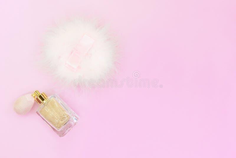 Το χρυσό μπεζ ακτινοβολεί χαλαρή σκόνη προσώπου με το σφουγγάρι ψεκαστήρων και ριπών στο ρόδινο υπόβαθρο στοκ εικόνα