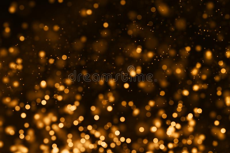 Το χρυσό σπινθήρισμα κλίσης Χριστουγέννων ακτινοβολεί μόρια σκόνης από την κορυφή στοκ εικόνα