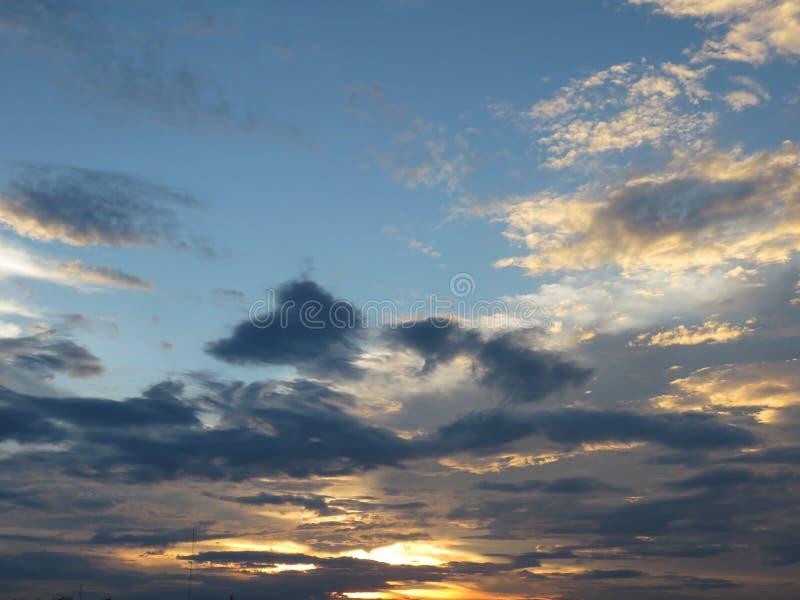το χρυσό φως του ήλιου βραδιού λάμπει μέσω των σύννεφων στον ουρανό στοκ φωτογραφίες