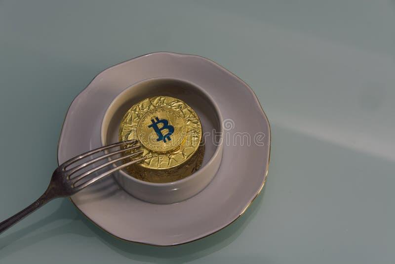 Το χρυσό bitcoin βρίσκεται στο άσπρο φλυτζάνι στο πιατάκι με το ασημένιο δίκρανο στοκ φωτογραφίες