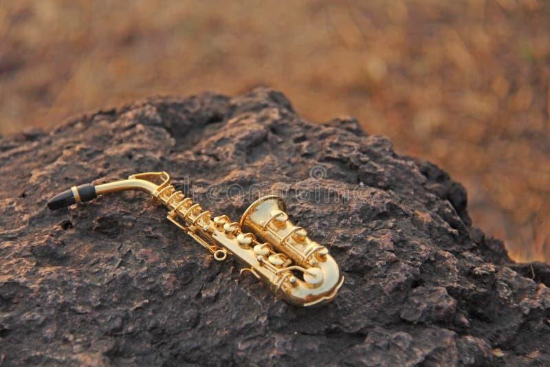 Το χρυσό saxophone alto βρίσκεται σε μια μαύρη πέτρα Ρομαντικό μουσικό υπόβαθρο Μουσική κάλυψη και δημιουργικός Σχέδιο με το διάσ στοκ φωτογραφίες