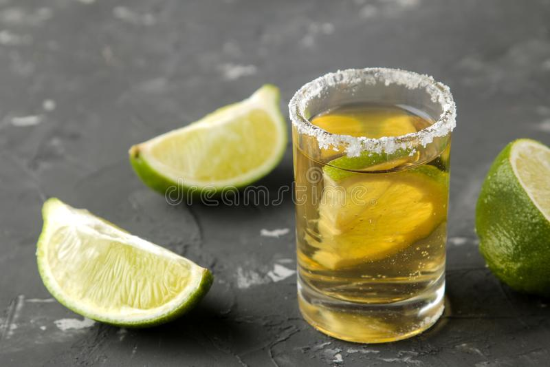 Το χρυσό tequila σε ένα γυαλί πυροβόλησε το γυαλί με στενό επάνω άλατος και ασβέστη σε ένα μαύρο συγκεκριμένο υπόβαθρο ράβδος οιν στοκ εικόνες