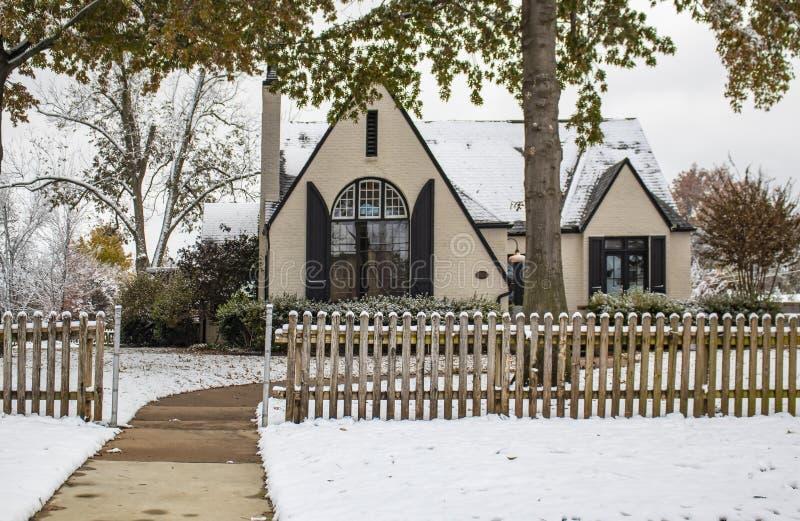 Το χρωματισμένο εξοχικό σπίτι τούβλου με το δραματικό μπροστινό παράθυρο και τα παραθυρόφυλλα πίσω από τον αγροτικό ξύλινο φράκτη στοκ εικόνες