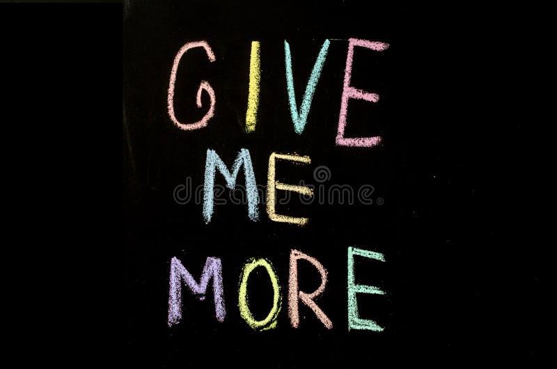 """Το χρωματισμένο κείμενο """"με δίνει περισσότερο """"που γράφομαι στον πίνακα κιμωλίας στοκ εικόνες"""