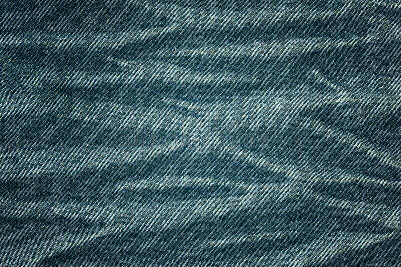 Το χρώμα τόνισε κοντά επάνω την εικόνα του ρυτιδωμένου υποβάθρου υφάσματος τζιν στοκ εικόνα