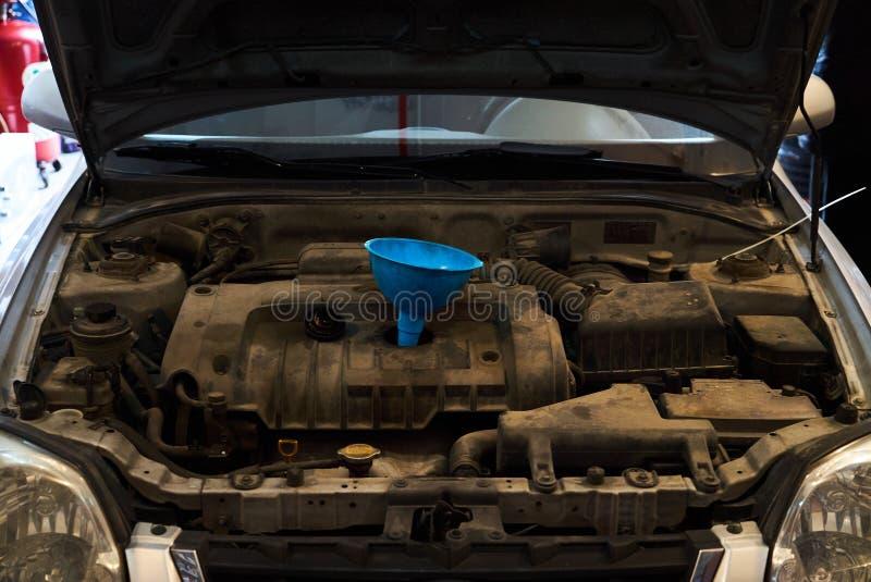 Το χύνοντας πετρέλαιο χοανών στη μηχανή αυτοκινήτων, κλείνει επάνω Αλλάξτε το πετρέλαιο αυτοκινήτων στοκ εικόνα