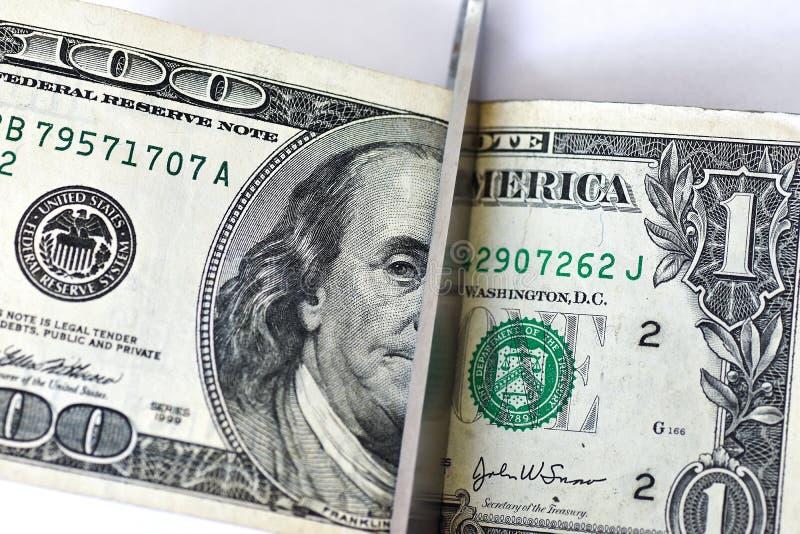 Το ψαλίδι έννοιας έκοψε το λογαριασμό εκατό δολαρίων και ενός δολαρίου στο άσπρο υπόβαθρο στοκ φωτογραφίες