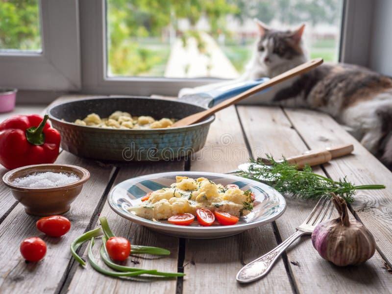 Το ψημένο κουνουπίδι στα καρυκευμένα αυγά και τα krsany λαχανικά σε έναν παλαιό ξύλινο πίνακα, στο υπόβαθρο βρίσκεται μια γάτα στ στοκ φωτογραφίες με δικαίωμα ελεύθερης χρήσης
