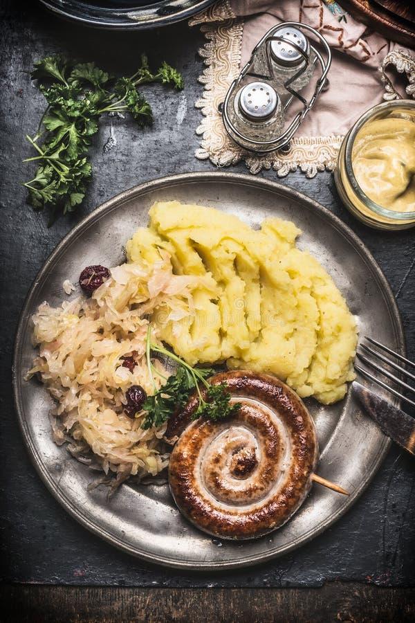 Το ψημένο λουκάνικο με τις πολτοποιηίδες πατάτες και το παστωμένο λάχανο στο μεταλλικό πιάτο με τα μαχαιροπήρουνα εξυπηρέτησαν στ στοκ εικόνες με δικαίωμα ελεύθερης χρήσης