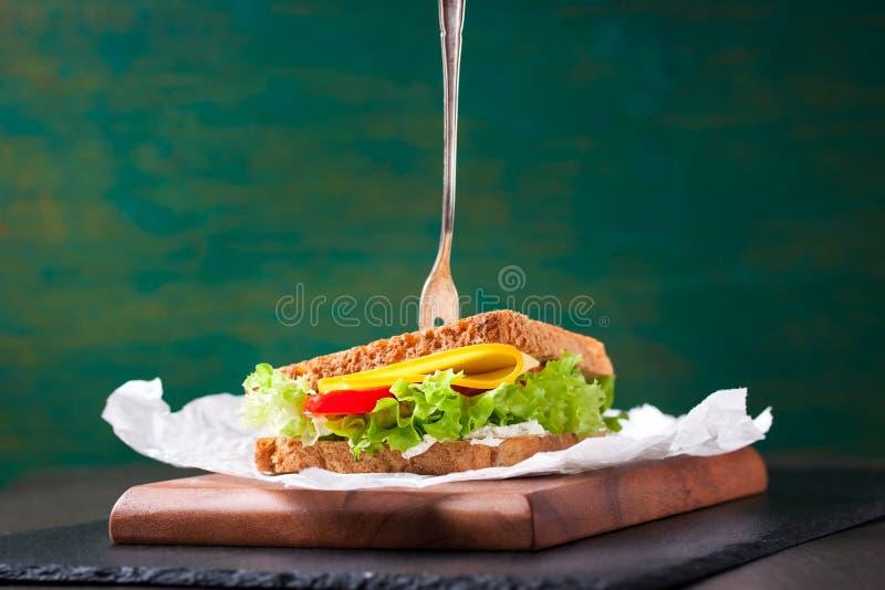 Το ψημένο σάντουιτς με τα φύλλα σαλάτας, οι ντομάτες και το τυρί με το δίκρανο σε μια κοπή επιβιβάζονται σε ένα πράσινο υπόβαθρο στοκ φωτογραφίες