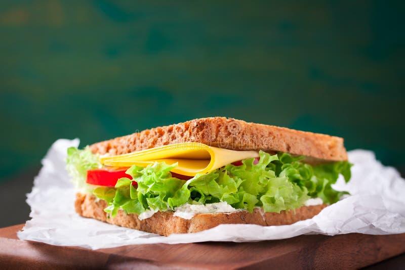 Το ψημένο σάντουιτς με τα φύλλα σαλάτας, οι ντομάτες και το τυρί με το δίκρανο σε μια κοπή επιβιβάζονται σε ένα σκοτεινό υπόβαθρο στοκ φωτογραφίες