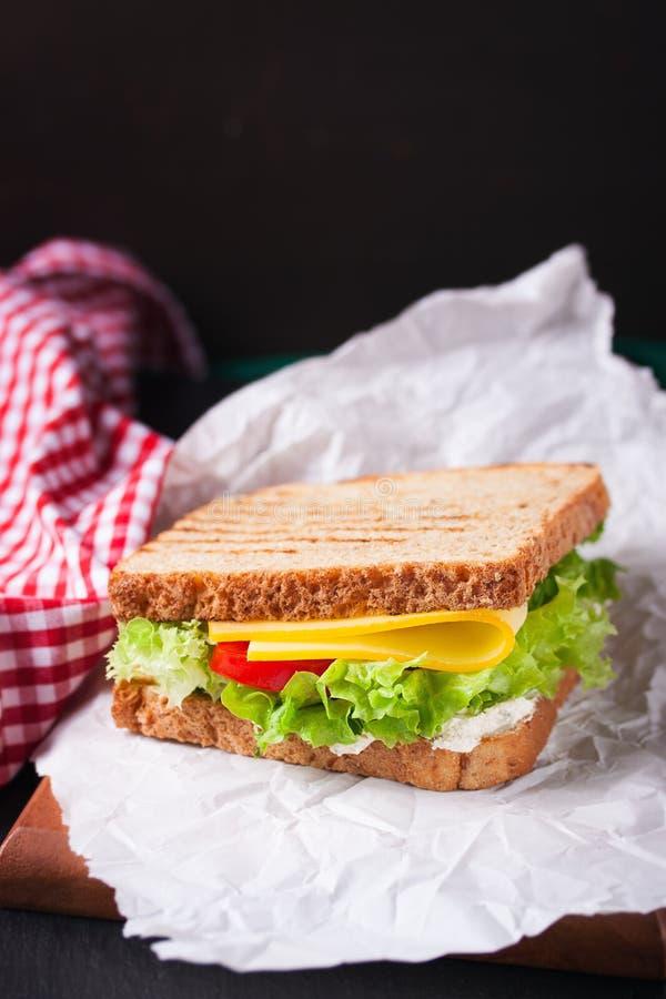 Το ψημένο σάντουιτς με τα φύλλα σαλάτας, οι ντομάτες και το τυρί με το δίκρανο σε μια κοπή επιβιβάζονται σε ένα σκοτεινό υπόβαθρο στοκ εικόνα με δικαίωμα ελεύθερης χρήσης