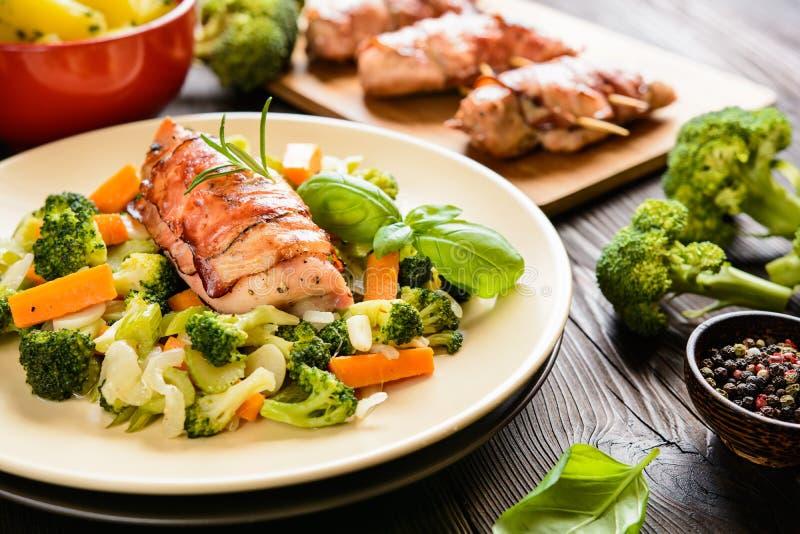 Το ψημένο στήθος κοτόπουλου τύλιξε στο μπέϊκον με τις βρασμένες πατάτες και το βρασμένο στον ατμό λαχανικό διακοσμεί στοκ φωτογραφία με δικαίωμα ελεύθερης χρήσης