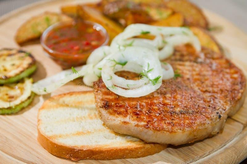 Το ψημένο στη σχάρα κρέας κοτόπουλου με τα παστωμένα κρεμμύδια και τα κολοκύθια, τηγανισμένες πατάτες, εξυπηρέτησε στο ξύλινο πιά στοκ εικόνα